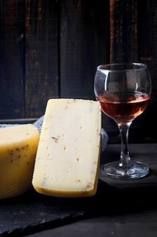 古い暗い木の板にラバンダーとテーブルにワインのグラスと自家製チーズの頭。新鮮な乳製品、健康的な有機食品。美味しい前菜。
