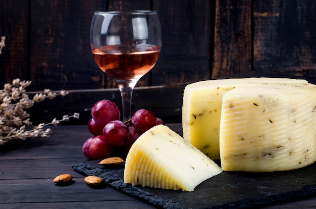 오래된 짙은 나무 판자에 라벤더가 있는 집에서 만든 치즈 머리와 테이블에 와인 한 잔. 신선한 유제품, 건강한 유기농 식품. 맛있는 전채.