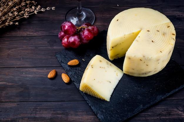 오래된 짙은 나무 판자에 라벤더가 있는 집에서 만든 치즈 머리와 테이블에 와인 한 잔.