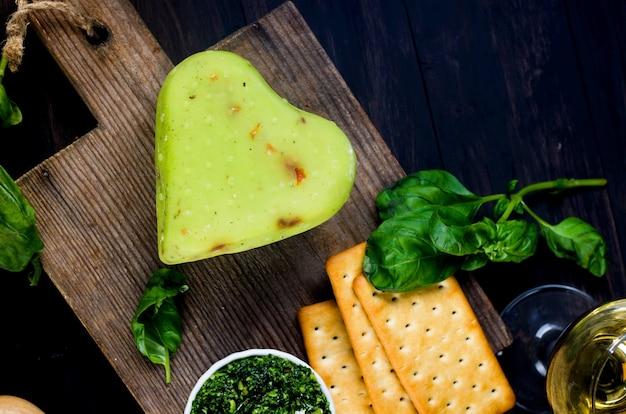 오래 된 어두운 나무 보드에 페스토 바질과 수제 치즈 머리