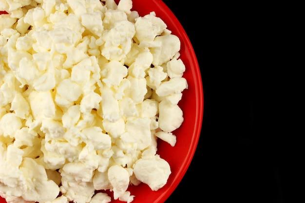 Домашний сыр на красной тарелке на черной поверхности