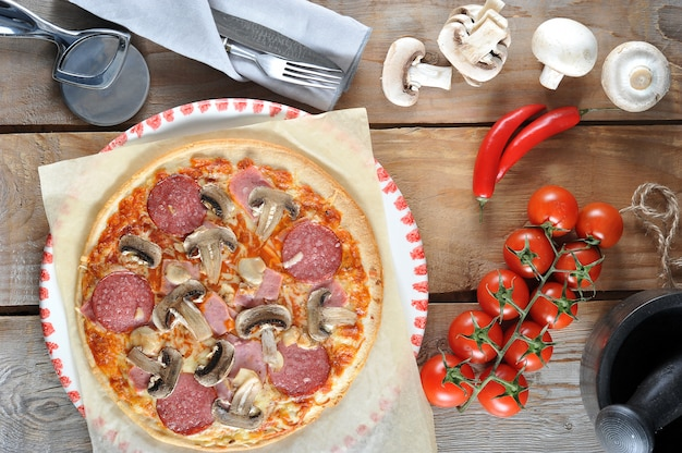 Homemade cheese pizza with salami and champignons