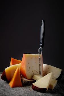 Домашние сырные ломтики ассорти с зелеными грушами и черным глазком на темном столе