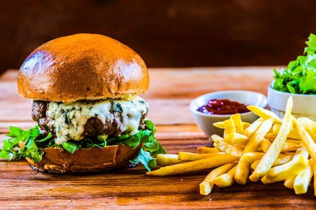 ブルーチーズと自家製チーズバーガー、フライドポテトと木製テーブルのサラダ添え