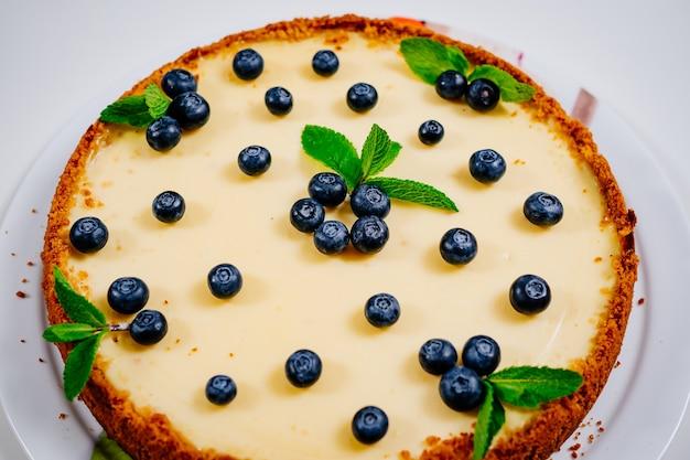 ブルーベリーベリーとミントの葉で飾られた自家製チーズケーキ。デザートやケーキを作る。