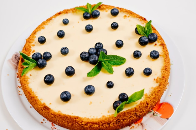 Homemade cheesecake decorated with blueberry berries and mint leaves. cooking desserts and cakes. confectionery.