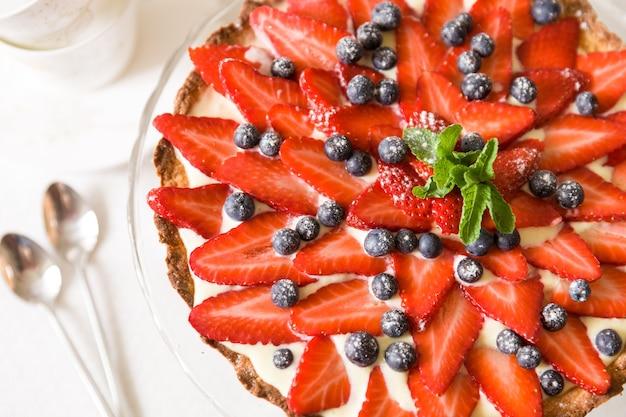 유기농 딸기 블루베리로 장식된 수제 치즈 케이크 신선한 민트와 크림 좋은 파이