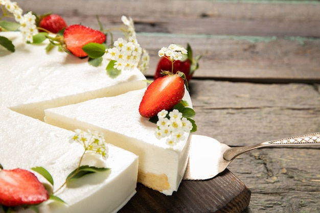 Homemade cheesecake decorated with strawberries on a wooden background
