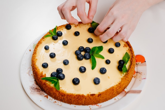 Homemade cheesecake hand decorating with blueberry berries and mint leaves. cooking desserts and cakes. confectionery.