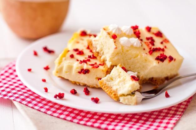 흰색 나무 표면에 말린 딸기와 수제 치즈 케이크 조각