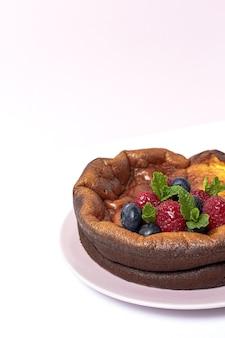 Домашний чизкейк с черникой, смородиной, клубникой и листьями мяты сверху. плоская планировка
