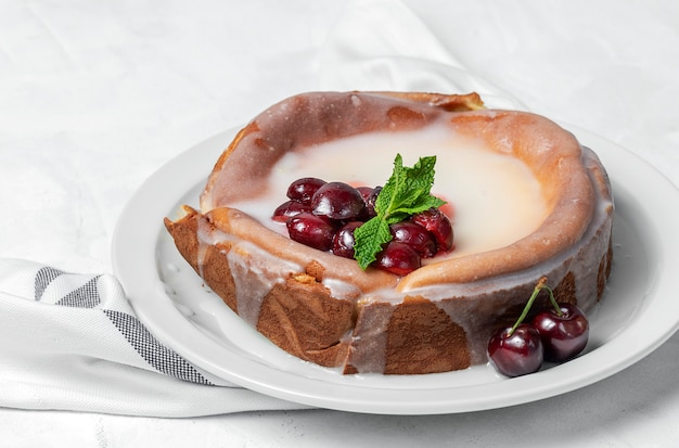 Homemade cheesecake with cherries and mint on white wall