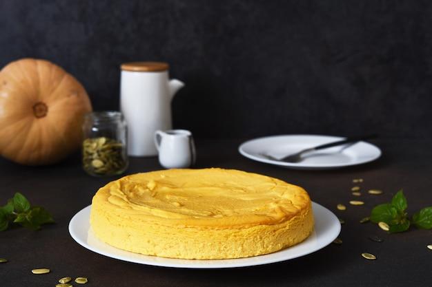 暗いコンクリートのテーブルの上にカボチャと自家製チーズケーキ。水平方向のフォーカス。