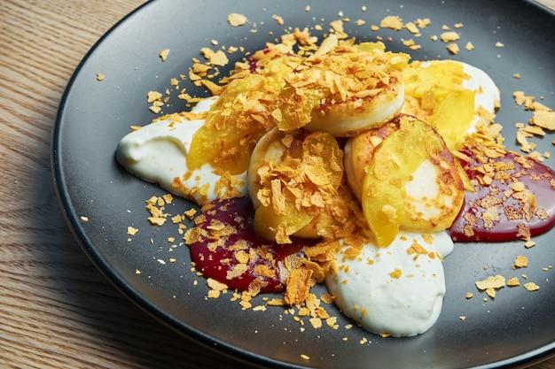 Домашние чизкейки или сырники с вареньем, тыквой и сметаной на черной тарелке на деревянной стене. украинская еда. завтрак еда