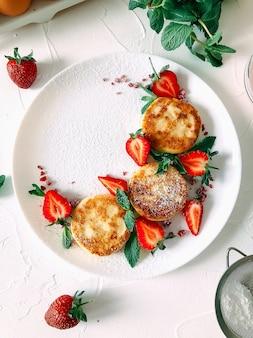 Домашние сырники, блины с клубникой на белой тарелке на белом текстурированном фоне