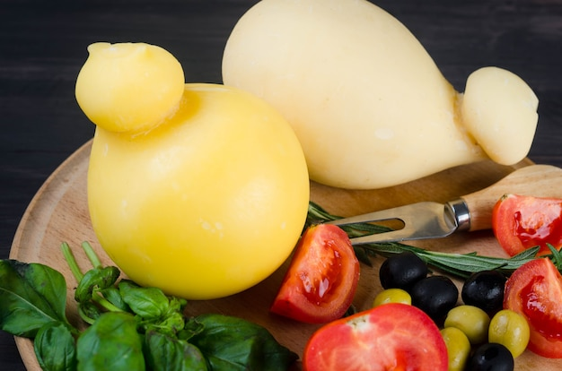 Домашняя сырная паста филата, проволоне на круглой деревянной доске на деревянном фоне. традиционный итальянский сыр caciocavallo и помидоры, перец, оливки, виноград, инжир и зелень