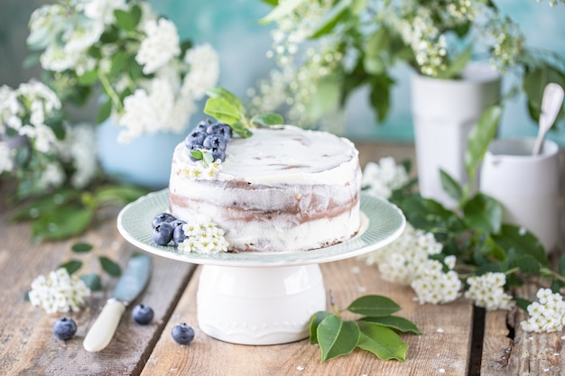 Homemade cherry cake with cream mascarpone on a light background and a bouquet of cherry flowers and lilacs.