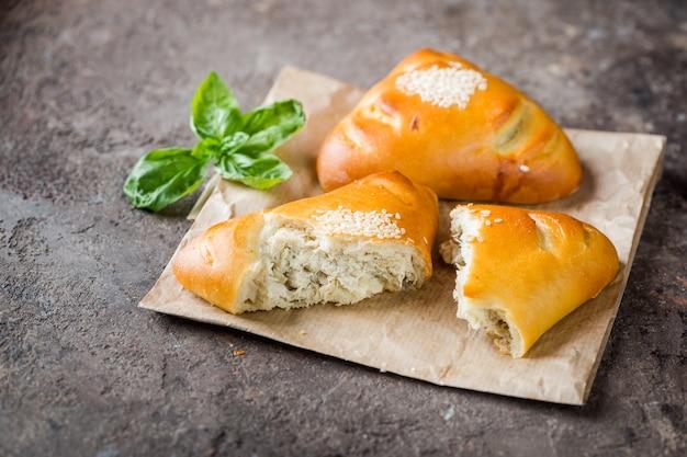 Домашние мини-пирожки с курицей и грибами на бумаге