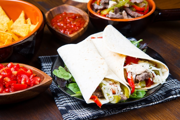 Homemade chicken and beef fajitas with vegetables and tortillas