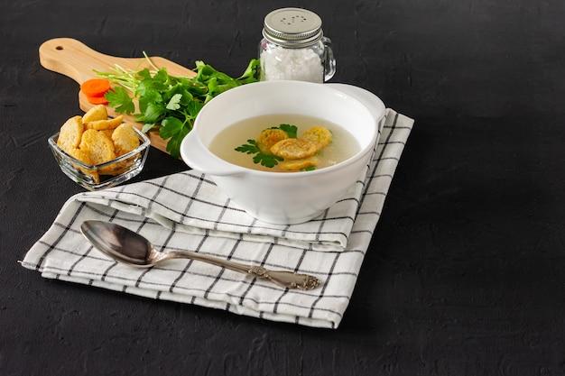 Домашний куриный бульон или бульон. здоровый завтрак. черный бетонный фон