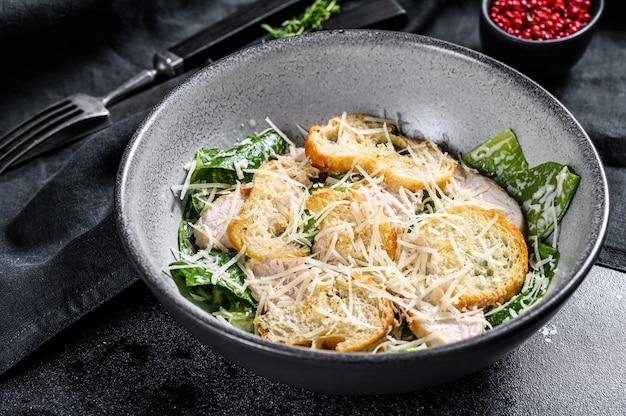 Домашний куриный салат цезарь с сыром и гренками. вид сверху