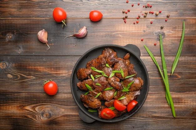 Домашняя куриная печень, обжаренная с соевым соусом, помидорами, луком и специями. закройте вверх. выборочный фокус. здоровая пища
