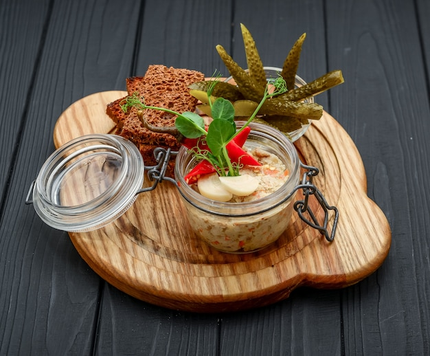 Homemade chicken liver pate in the jar on a rustic wooden table