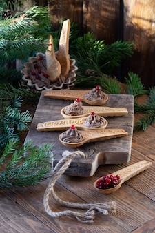 Домашний паштет из куриной печени с клюквой в съедобных песочных ложках на старой деревянной разделочной доске