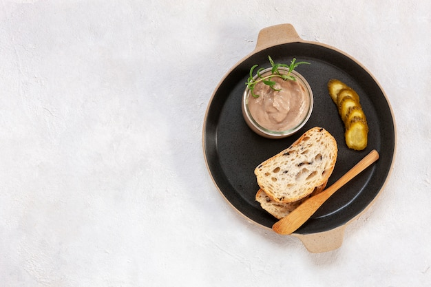 Homemade chicken liver pate with pickled cucumber and fresh crispy whole grain bread background