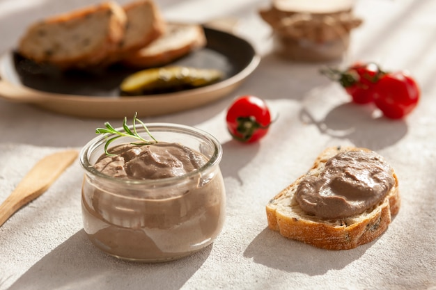 Homemade chicken liver pate with pickled cucumber and tomato and fresh crispy whole grain bread