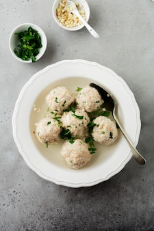 Homemade chicken matzo ball soup with parsley and garlic in simple white ceramic plate on a gray stone or concrete