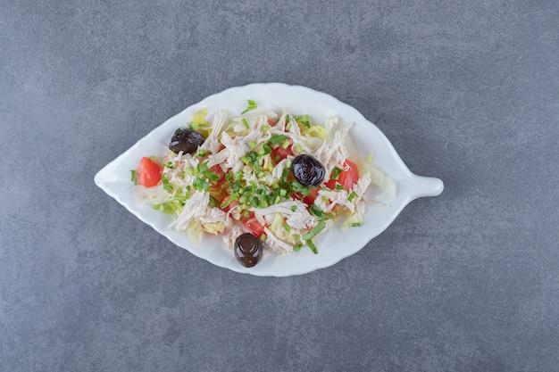 잎 모양의 접시에 홈메이드 치킨 샐러드입니다.