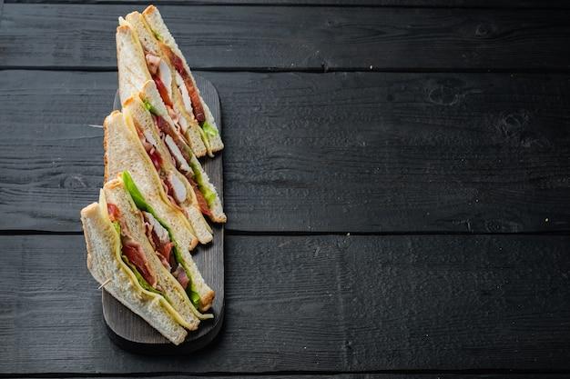 自家製チキンサンドイッチの半分、テキスト用のコピースペースのある黒い木製のテーブル