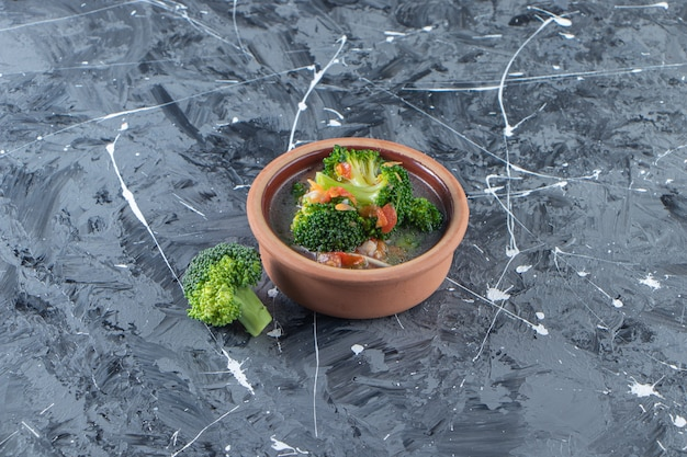 Домашний куриный суп в миске на мраморной поверхности.