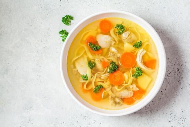 Домашний куриный суп с лапшой и овощами в белой миске