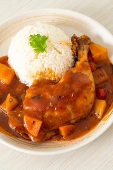 쌀과 함께 접시에 토마토, 양파, 당근, 감자를 곁들인 홈메이드 치킨 스튜