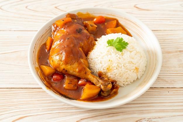Домашнее куриное рагу с помидорами, луком, морковью и картофелем на тарелке с рисом