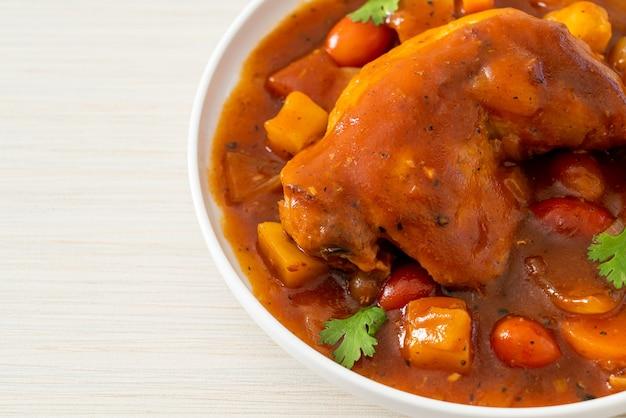 Домашнее куриное рагу с помидорами, луком, морковью и картофелем на тарелке