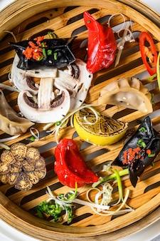 自家製の中華料理と韓国の餃子を伝統的な竹蒸し器で提供しています。灰色の背景。上面図