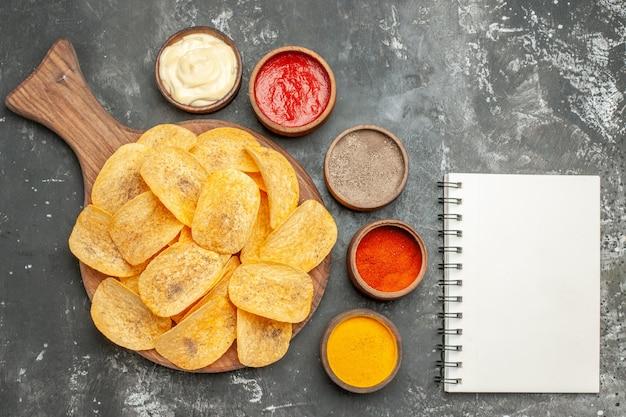 도마에 케첩과 회색 테이블에 노트북과 함께 만든 칩 향신료와 마요네즈