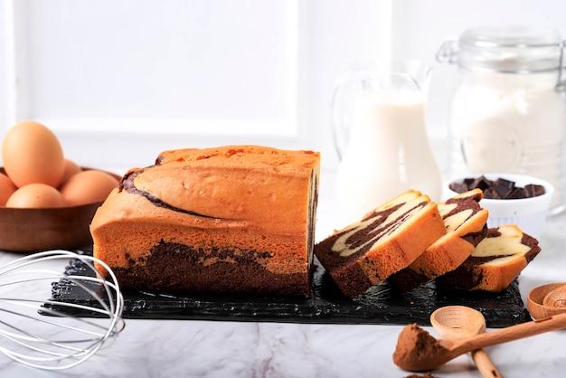 スライスケーキ、ヴィンテージベーカリーコンセプトの白い背景と黒い石のプレートに自家製チョコレートとバニラ大理石のローフ