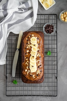 Homemade chocolate banana bread with chocolate cream, banana slices and nuts on top on a dark concrete background.