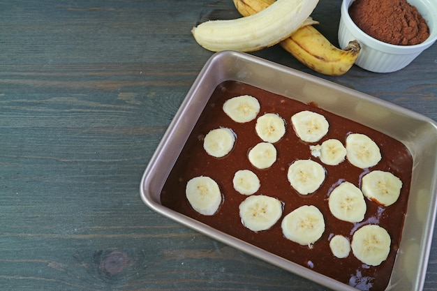 Homemade chocolate banana olive oil cake batter in cake pan with ripe bananas and cocoa powder