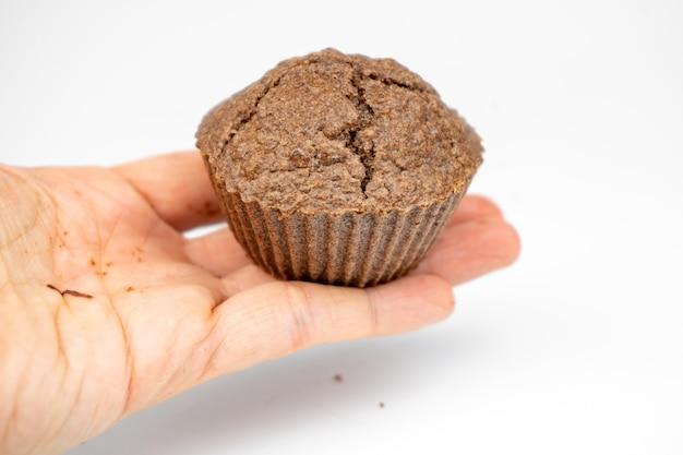 손에서 수 제 초콜릿 브라운 머핀입니다. 흰색 배경에 고립