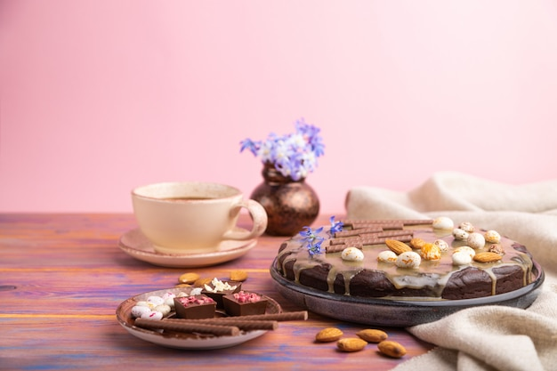 Homemade chocolate brownie cake with caramel cream and almonds with cup of coffee on a colored and pink background