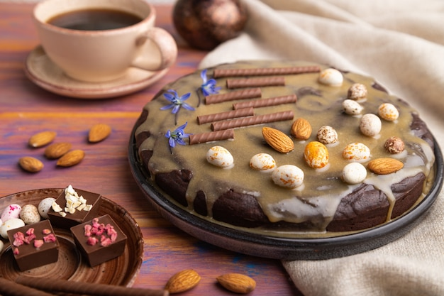 Homemade chocolate brownie cake with caramel cream and almonds with cup of coffee on a colored wooden background.