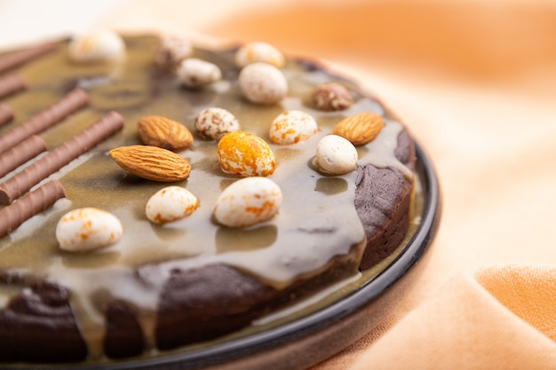 Homemade chocolate brownie cake with caramel cream and almonds with cup of coffee on a white concrete  background.