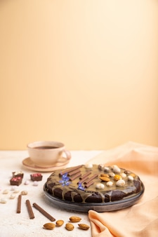Homemade chocolate brownie cake with caramel cream and almonds with cup of coffee on a white and orange background. side view, selective focus, copy space.