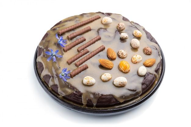 キャラメルクリームとアーモンドの白い背景で隔離の自家製チョコレートブラウニーケーキ。側面図。