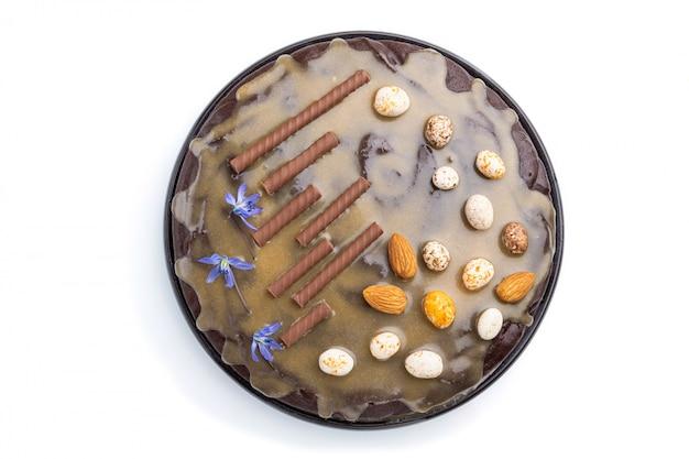 キャラメルクリームとアーモンドの白い背景で隔離の自家製チョコレートブラウニーケーキ。上面図。